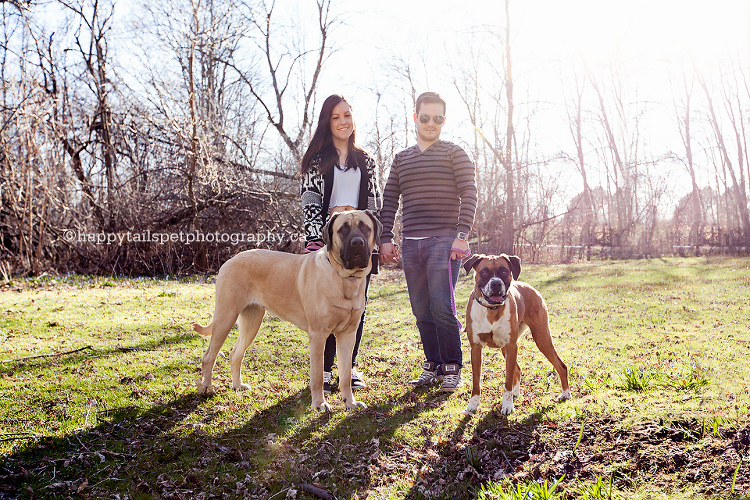 A young couple with two dogs in beautiful outdoor setting by Happy Tails Pet Photography in Oakville dog photography session.
