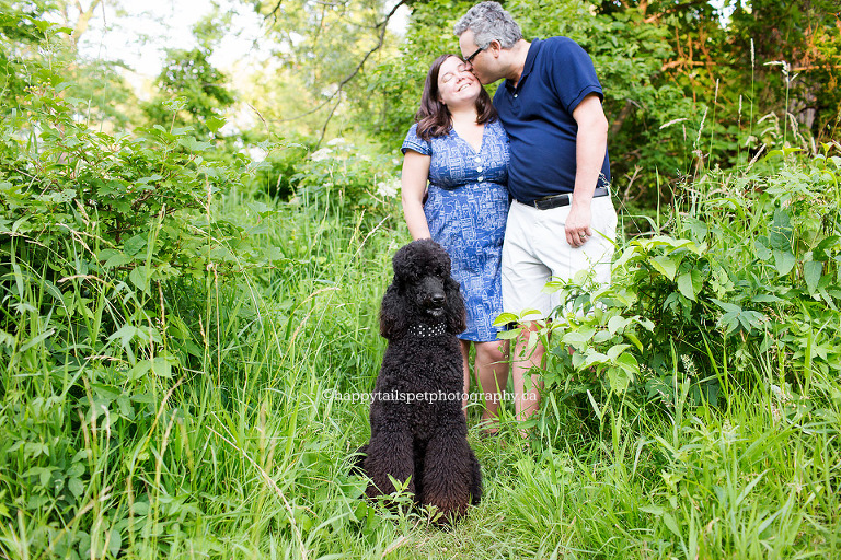 Cute couple snuggles while black poodle looks on at pet photography session at Ontario park.